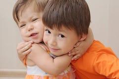 拥抱兄弟的小微笑的姐妹 库存图片