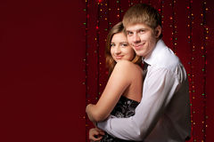 拥抱光背景的夫妇  免版税库存图片