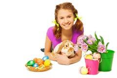 拥抱兔子用在地板上的东部鸡蛋的女孩 免版税图库摄影