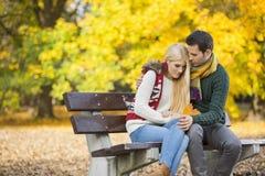 拥抱公园长椅的热情的年轻人害羞的妇女在秋天期间 库存照片