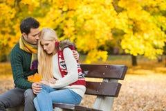 拥抱公园长椅的爱恋的年轻人害羞的妇女在秋天期间 免版税库存图片