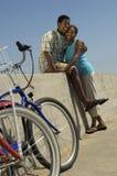 拥抱反对天空的夫妇乘自行车 免版税库存图片