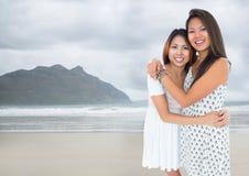 拥抱反对模糊的海滩的最好的朋友 图库摄影