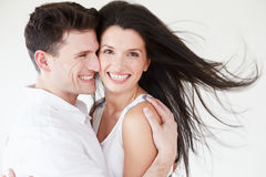 拥抱反对白色演播室背景的浪漫夫妇 免版税库存图片