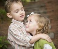 拥抱可爱的兄弟和姐妹的孩子外面 库存图片