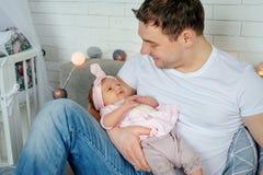 拥抱和亲吻他的甜可爱的婴儿的愉快的年轻父亲特写镜头画象  愉快概念的系列 库存照片