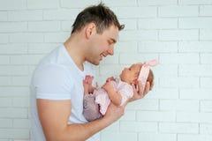 拥抱和亲吻他的甜可爱的婴儿的愉快的年轻父亲特写镜头画象  愉快概念的系列 免版税库存图片