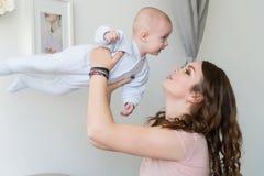 拥抱和亲吻他的甜可爱的孩子的愉快的年轻母亲特写镜头画象  户内射击了,概念图象 库存图片