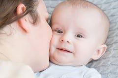 拥抱和亲吻他的甜可爱的孩子的愉快的年轻母亲特写镜头画象  户内射击了,概念图象 免版税库存图片