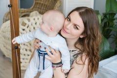 拥抱和亲吻他的甜可爱的孩子的愉快的年轻母亲特写镜头画象  户内射击了,概念图象 免版税库存照片
