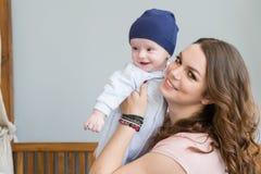 拥抱和亲吻他的甜可爱的孩子的愉快的年轻母亲特写镜头画象  户内射击了,概念图象 库存照片