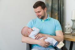 拥抱和亲吻他的甜可爱的孩子的愉快的年轻父亲特写镜头画象  户内射击了,概念图象 库存照片