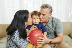 拥抱和亲吻儿子的父母 库存图片