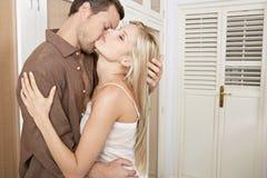 拥抱和亲吻在卧室的夫妇。 免版税库存图片