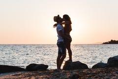 拥抱和亲吻在海滩的年轻夫妇 库存图片