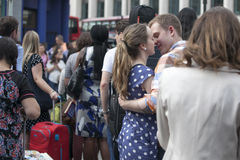 拥抱和亲吻在高峰时间的年轻爱恋的夫妇在地铁科文特花园附近 免版税库存照片