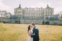 拥抱和亲吻在绿色晴朗的草坪的有吸引力的新婚佳偶对在美丽的被破坏的巴洛克式的宫殿附近 库存图片