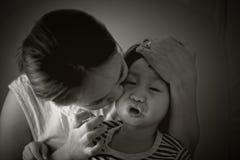 拥抱和亲吻她的儿子的愉快的母亲 库存图片