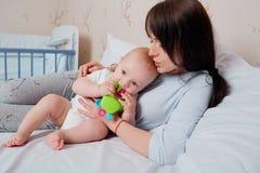 拥抱和亲吻她的充满爱的有同情心的母亲婴孩 照顾a 库存照片