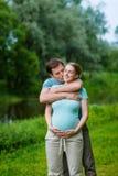 拥抱和亲吻他怀孕的妻子的愉快的微笑的英俊的人 库存图片
