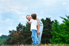 拥抱和亲吻他愉快的母亲的爱恋的儿子  免版税库存照片