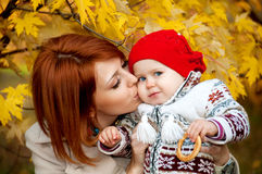 拥抱和亲吻他的小女儿的美丽的母亲 免版税库存图片