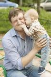 拥抱和亲吻他的父亲的儿子 库存照片