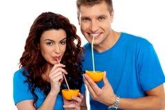 拥抱和啜饮橙汁的夫妇 库存照片