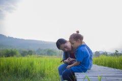 拥抱和安慰一个哭泣的小长发男孩,亚裔母亲的年轻母亲设法安慰和使她哭泣的孩子镇静下来 免版税库存图片