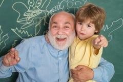 拥抱和容忍 他的喜欢谈与祖父 学习和教育概念 教她的儿子的父亲在教室 库存照片