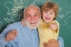 拥抱和容忍 祖父和孙子 帮助有教训的老师年轻男孩 ?? 库存照片