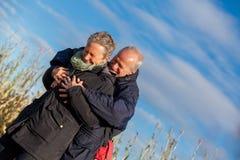 拥抱和庆祝太阳的年长夫妇 库存照片