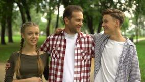 拥抱和微笑入照相机的快乐的家庭在公园,信任的关系 影视素材
