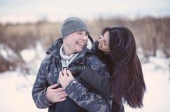 拥抱和微笑在冬天公园的美好的年轻夫妇 愉快的系列 库存图片