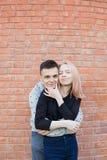 拥抱和微笑在红砖墙壁背景的愉快的年轻夫妇  有蓝眼睛的白肤金发的女孩和阿拉伯appea的一个年轻人 库存图片