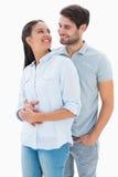 拥抱和微笑对彼此的逗人喜爱的夫妇 免版税图库摄影