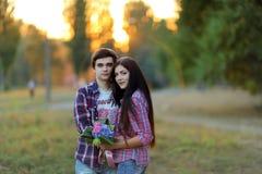 拥抱和微笑对日落的年轻美好的夫妇在夏天 库存照片