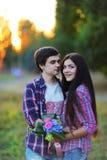 拥抱和微笑对日落的年轻美好的夫妇在夏天 图库摄影