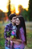 拥抱和微笑对日落的年轻美好的夫妇在夏天 免版税库存照片