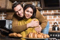 拥抱和微笑对照相机的愉快的年轻不同种族的夫妇在早餐期间 免版税库存图片