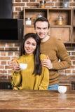 拥抱和微笑对照相机的愉快的年轻不同种族的夫妇,当喝咖啡时 库存图片