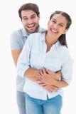 拥抱和微笑对照相机的逗人喜爱的夫妇 库存图片