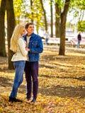 拥抱和挥动在公园的年轻夫妇 免版税库存图片