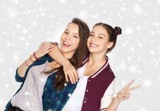 拥抱和显示和平标志的愉快的十几岁的女孩 免版税库存照片
