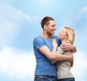 拥抱和看彼此的微笑的夫妇 免版税库存图片