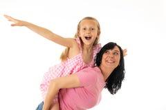 拥抱和看快乐照相机的一个愉快的母亲和逗人喜爱的白肤金发的小女孩的画象在白色背景的演播室 H 库存照片