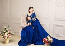 拥抱和看照相机的母亲和女儿 系列愉快爱 母亲和女儿美好的长的豪华蓝色dres的 库存图片