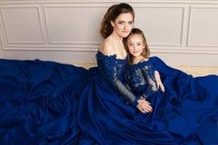 拥抱和看照相机的母亲和女儿 系列愉快爱 母亲和女儿美好的长的豪华蓝色dres的 库存照片
