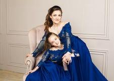 拥抱和看照相机的母亲和女儿 系列愉快爱 母亲和女儿美好的长的豪华蓝色dres的 免版税库存照片