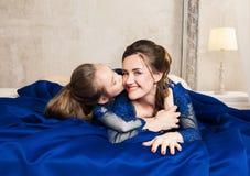 拥抱和看照相机的母亲和女儿 系列愉快爱 母亲和女儿美好的长的豪华蓝色dres的 免版税库存图片